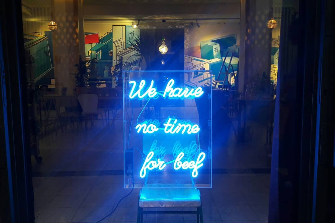 """Neonschild im Café sagt """"we have no time for beef"""""""